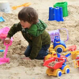 A boy playing with the buckets and spades in the sand pit