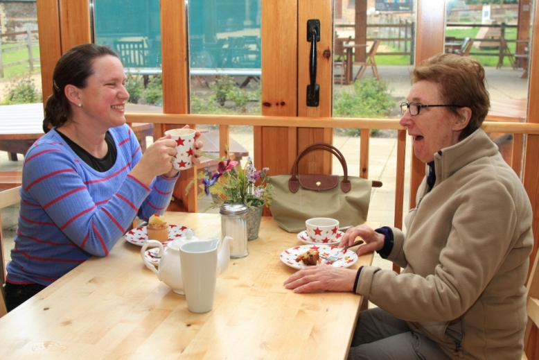 A couple of ladies enjoying a nice cup of tea and a slice of cake