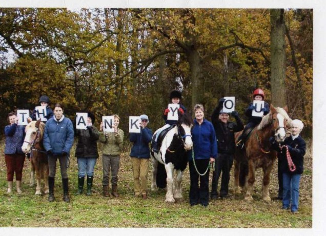 Members of the Riding for the disabled group holding up letters to make the work Than you