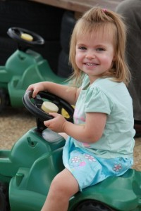 A little girl playing n the push along tractors