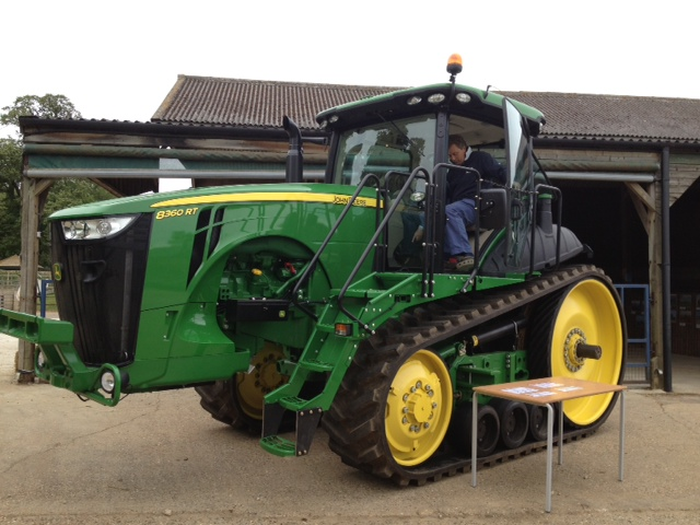 A John Deere green and yellow tractor with caterpillar tracks, not wheels