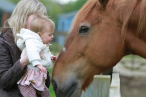 A little girl and her mother stoking Belle