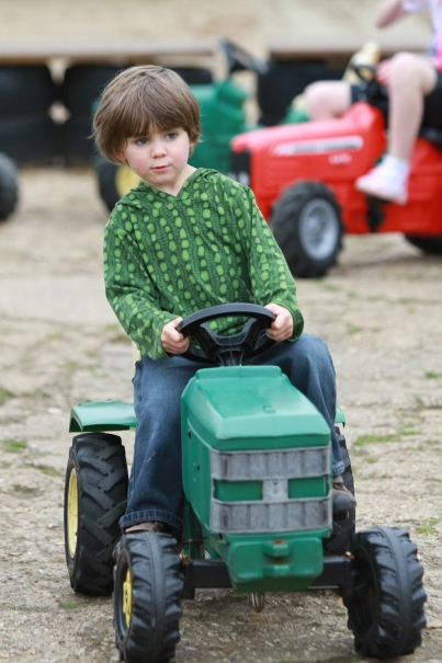 A little boy playing on the green pedal tractors in the playground
