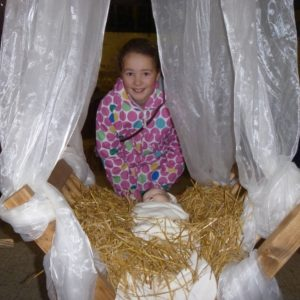 A little girl looking at the crib with baby Jesus lying in the straw