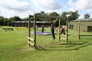 Children playing on the monkey bars and trampolines in the outdoor playarea