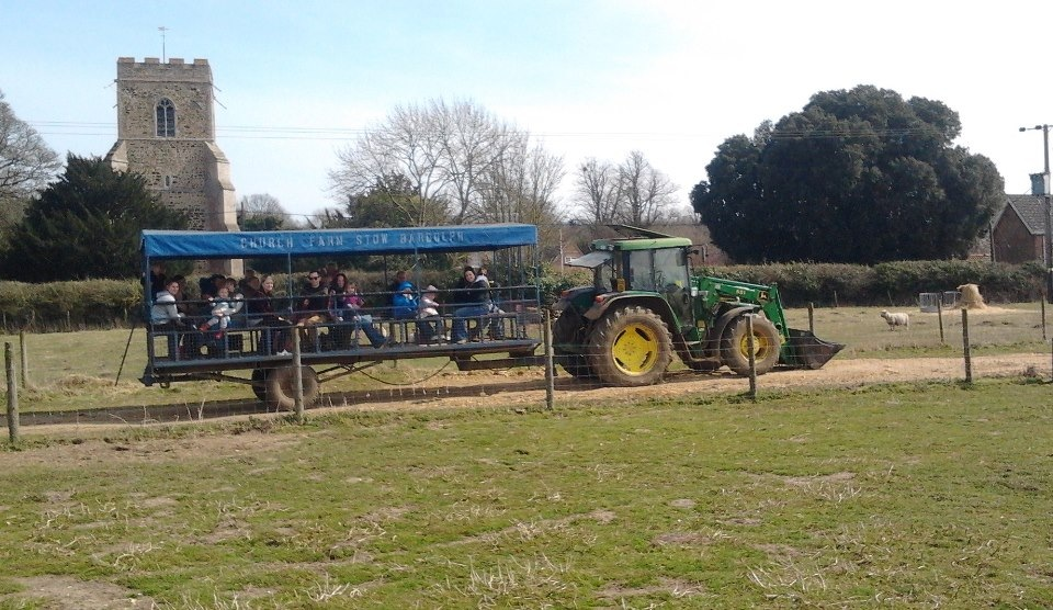 A tractor pulling a trailer full of visitors with the church in the background